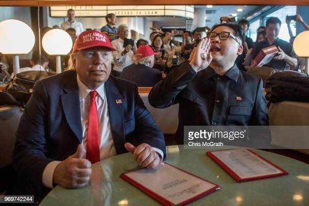 Kim Jong Un impersonator Howard X and Donald Trump impersonator Dennis Alan sit in a restaurant during a visit to the famous Merlion Park on June 8...