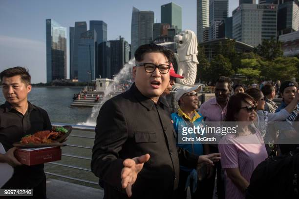 Kim Jong Un impersonator Howard X and Donald Trump impersonator Dennis Alan pose for photographers during a visit to the famous Merlion Park on June...