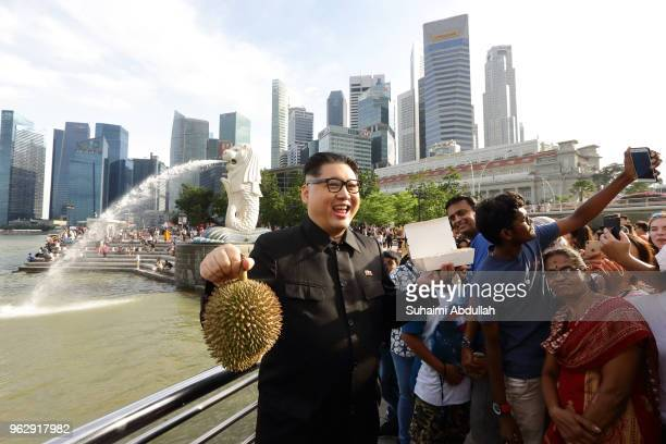 Kim Jong Un impersonator Howard X makes an appearance with Singapore's local food chicken rice and durian at Merlion Park on May 27 2018 in Singapore...
