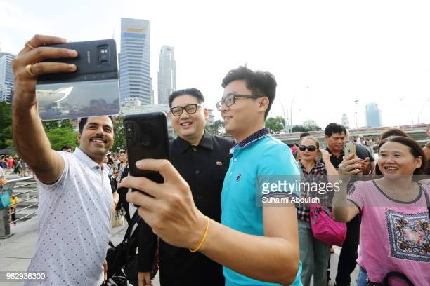 Kim Jong Un impersonator Howard X poses for a photo with tourists at Merlion Park on May 27 2018 in Singapore The proposed North KoreaUnited States...