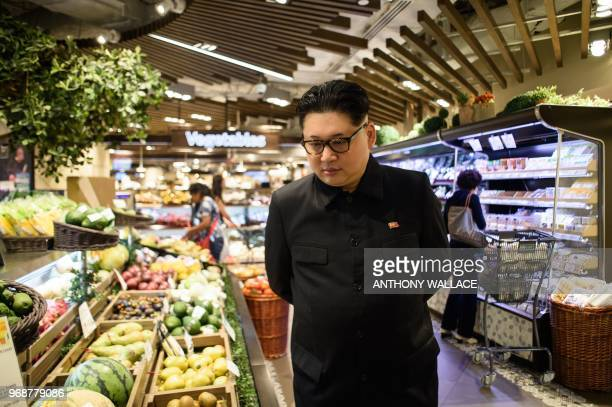 Kim Jong Un impersonator who goes by the name Howard X looks at fruit while dressed up as the North Korean leader in a supermarket in Hong Kong on...