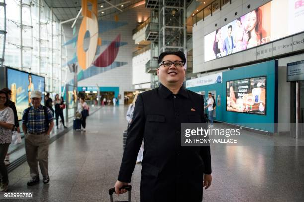 A Kim Jong Un impersonator who goes by the name Howard X walks with luggage that he borrowed from a passenger in the Airport Express train station in...