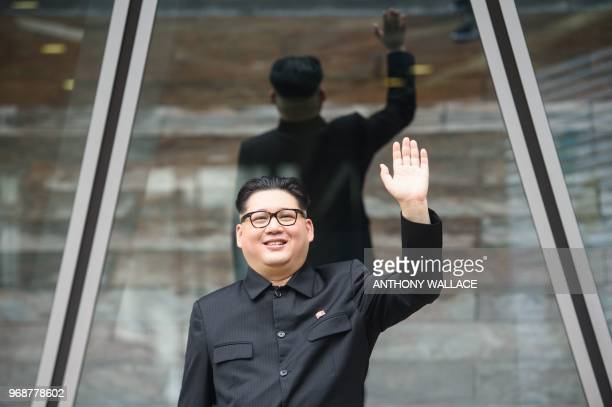 TOPSHOT Kim Jong Un impersonator who goes by the name Howard X waves outside a building while dressed up as the North Korean leader in Hong Kong on...