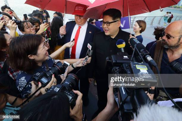 Kim Jongun impersonator Howard X and Donald Trump impersonator Dennis Alan speaks to the media at Merlion Park on June 8 2018 in Singapore The White...