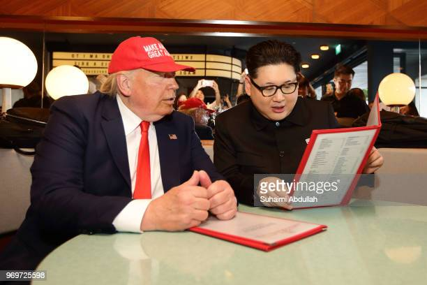 Kim Jongun impersonator Howard X and Donald Trump impersonator Dennis Alan looks to order for drinks at Merlion Park on June 8 2018 in Singapore The...