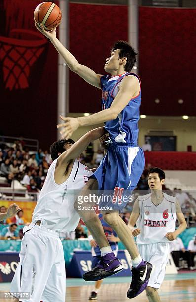 Kim Joo Sung of the Republic of Korea shoots over the defense of Japan during the Men's Basketball Classification during the 15th Asian Games Doha...