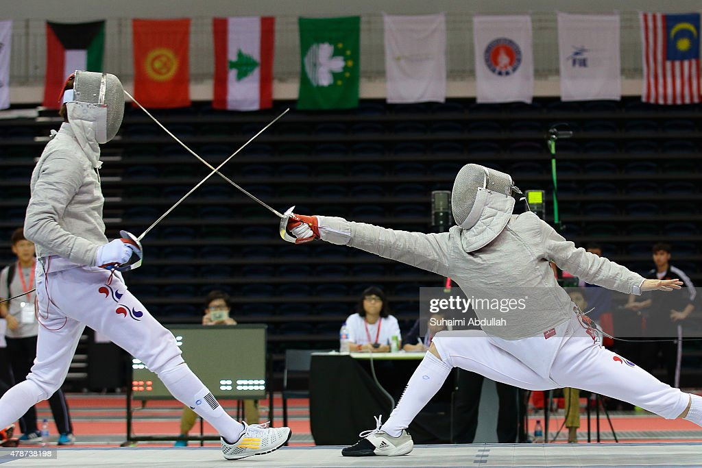 Kim Junghwan of South Korea (L) and Gu Bongil of South Korea compete in the men's individual sabre final during the 2015 Asian Fencing Championships at OCBC Arena on June 27, 2015 in Singapore.