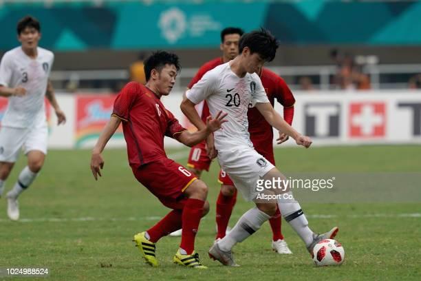 Kim Jungmin of South Korea battles Luong Xuan Truong of Vietnam during the Men's Footbal semi final competition between Vietnam and South Korea held...