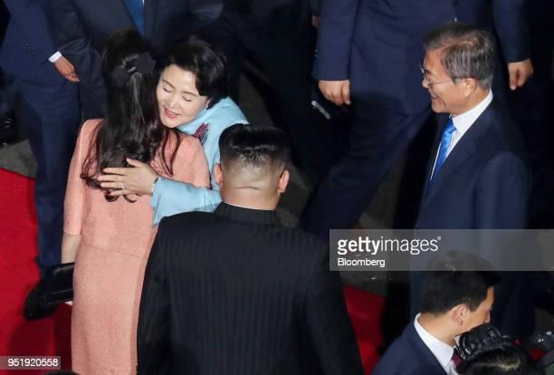 Kim Jungsook South Korea's first lady second left and Ri Sol Ju North Korea's first lady left embrace as Kim Jong Un North Korea's leader center and...