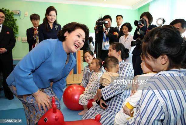 Kim Jungsook wife of South Korean President Moon Jaein greets North Korean children as Ri Sol Ju wife of North Korean leader Kim Jong Un looks on...