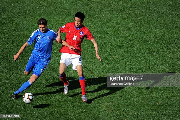 Kim JungWoo of South Korea challenges Angelos Charisteas of Greece during the 2010 FIFA World Cup South Africa Group B match between South Korea and...