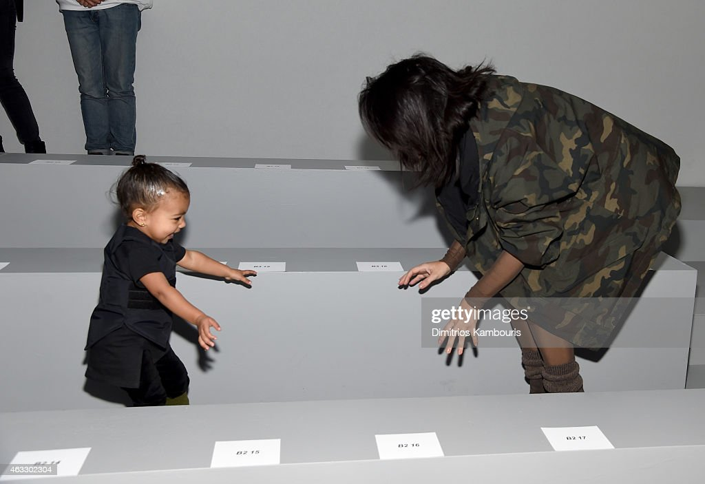 Kim Kardashian (R) and daughter North attend the adidas Originals x Kanye West YEEZY SEASON 1 fashion show during New York Fashion Week Fall 2015 at Skylight Clarkson Sq on February 12, 2015 in New York City.