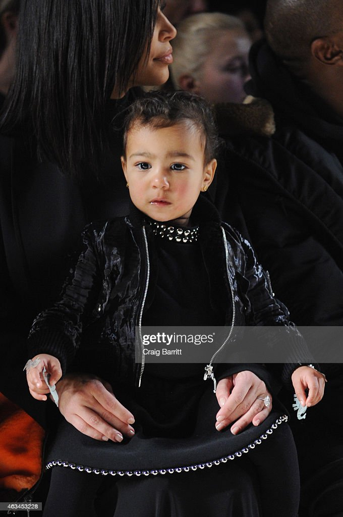 Kim Kardashian (L) and North West attend the Alexander Wang Fashion Show during Mercedes-Benz Fashion Week Fall 2015 at Pier 94 on February 14, 2015 in New York City.