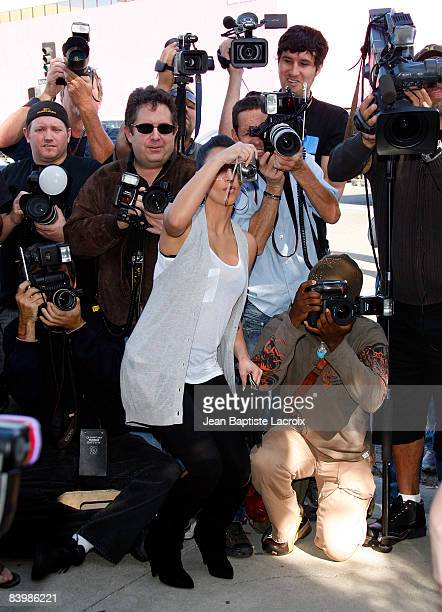 Kim Kardashian jumps in with the other photographers at the unveiling of Khloe Kardashian's PETA Fur I'd Rather Go Naked Billboard on December 10...