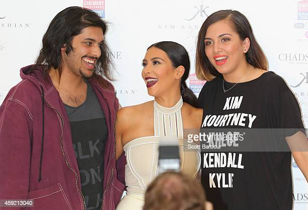 Kim Kardashian poses for a photograph with fans as she promotes her new fragrance Fleur Fatale at Chadstone Shopping Centre on November 19 2014 in...