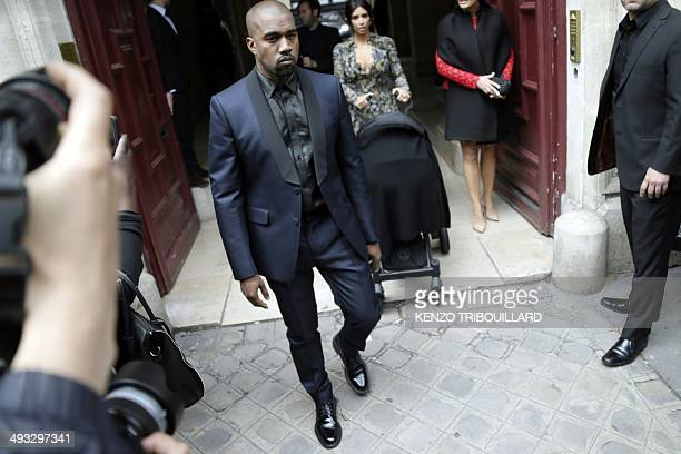 Kim Kardashian pushes a stroller next to her partner Kanye West and her mother Kris Jenner as they leave their hotel on May 23 2014 in Paris Hip hop...