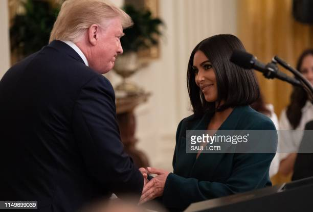 Kim Kardashian shakes hands with US President Donald Trump during a second chance hiring and criminal justice reform event in the East Room of the...