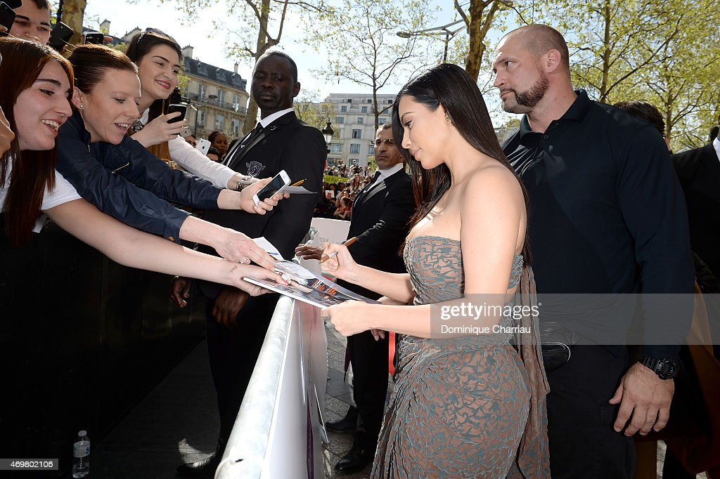 Kim Kardashian signs autographs before she introduces her 'Kardashian Beauty Hair' line at Marionnaud Champs Elysees on April 15, 2015 in Paris, France.