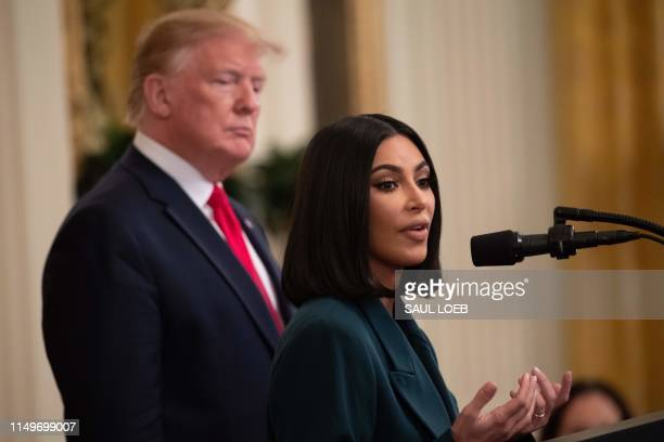 Kim Kardashian speaks alongside US President Donald Trump during a second chance hiring and criminal justice reform event in the East Room of the...