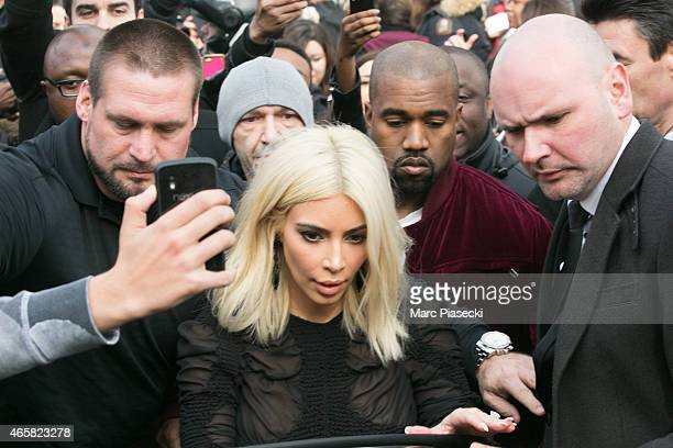 Kim Kardashian West and husband Kanye West leave the 'Louis Vuitton' fashion show surrounded by fans on March 11 2015 in Paris France