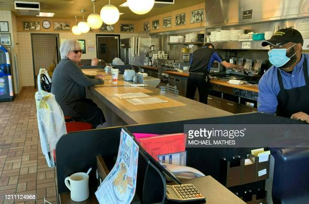 Kim Kaseta sits at the counter of a Waffle House for breakfast in Atlanta, as the state of Georgia relaxed its Coronavirus pandemic restrictions to...