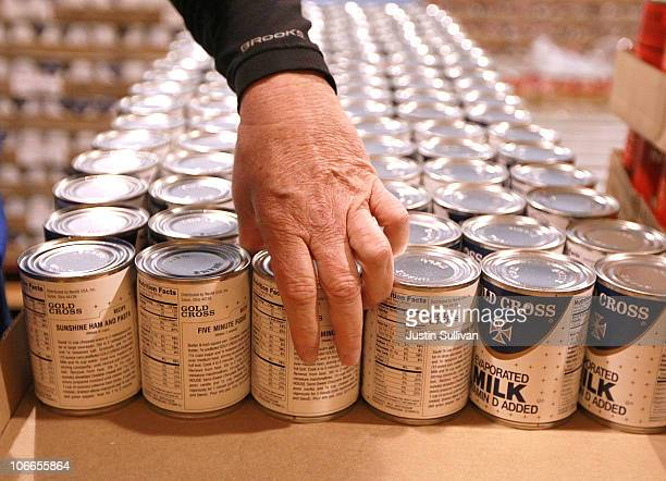 Kim Kinker packs cans of evaporated milk into boxes while volunteering with members of the San Francisco 49ers at the San Francisco Food Bank on...