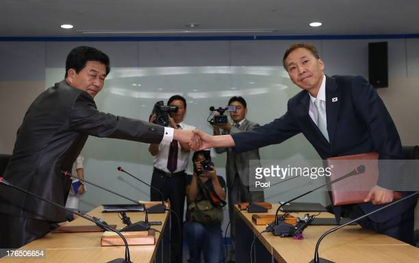 Kim KiWoong the head of South Korea's workinglevel delegation and his North Korean counterpart Park CholSu exchange agreement documents after their...