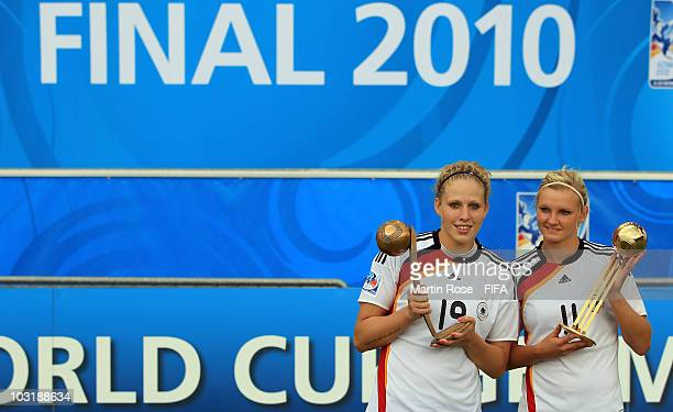 Kim Kulig of Germany and Alexandra Popp pose with the bronze and golden trophy after the 2010 FIFA Women's World Cup Final match between Germany and...