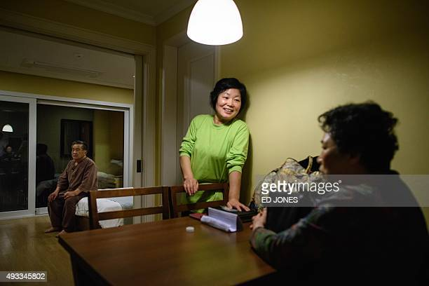 Kim KunHo sits on his bed as his niece Nam JongUn talks with his wife Kim OkJa the night before they depart their North Korean relatives at a family...