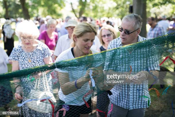 Kim Leadbeater the sister of murdered Member of Parliament Jo Cox joins others in symbolically tying a ribbon onto a piece of netting during a 'Great...