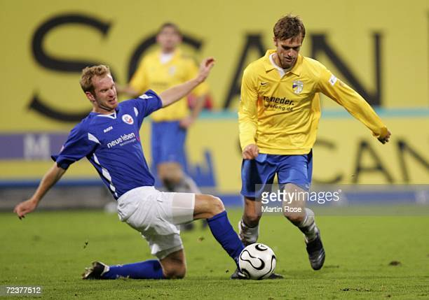 Kim Madsen of Rostock tries to stop Fiete Sykora of Jena during the Second Bundesliga match between Hansa Rostock and Carl Zeiss Jena at the Ostsee...