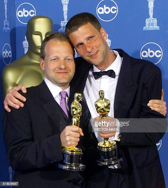 """Kim Magnusson and Anders Thomas Jensen hold each other as they pose with their Oscars for Best Live Actor Short Films for """"Election Night"""" at the..."""