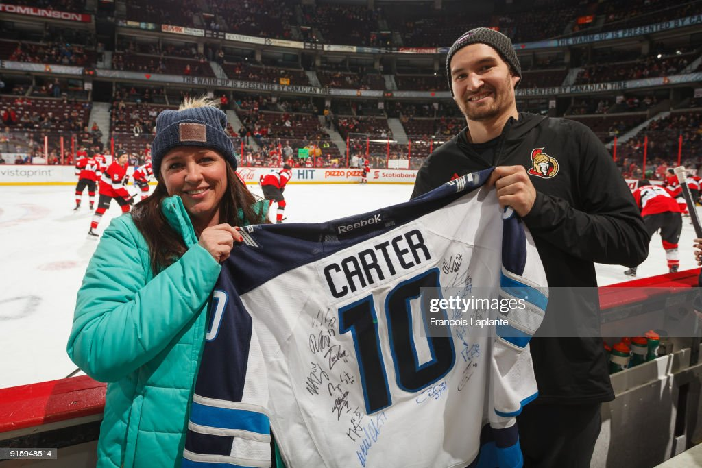 Kim Matthews poses along with Mark Stone #61 of the Ottawa Senators with the traveling jersey on the bench during warmup prior to the game against the Nashville Predators at Canadian Tire Centre on February 9, 2018 in Ottawa, Ontario, Canada.