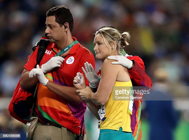 Kim Mickle of Australia is assisted by medical staff after being injured during the Women's Javelin Throw Qualifying Round on Day 11 of the Rio 2016...