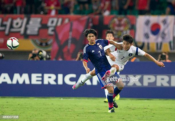 Kim Minwoo of South Korea and Gaku Shibasaki of Japan vie for the ball in group match between Japan and South Korea during EAFF East Asian Cup 2015...