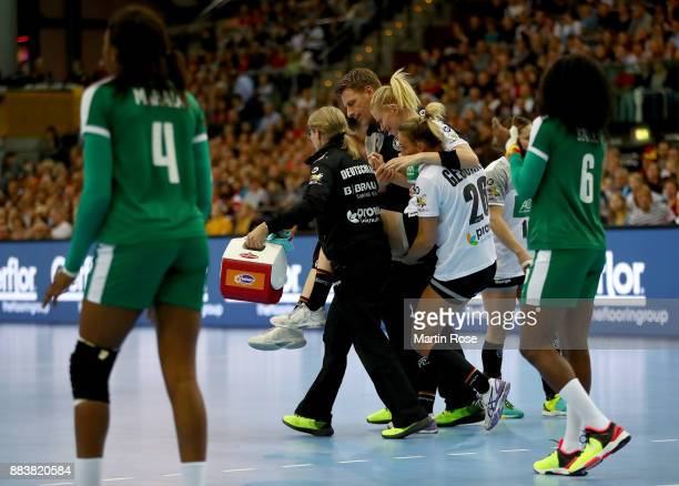 Kim Naidzinavicius of Germany is carried injured off the field during the IHF Women's Handball World Championship group D match between Germany and...