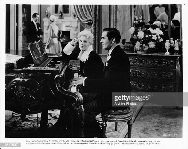 Kim Novak listens as Tyrone Power plays piano in a scene from the film 'The Eddy Duchin Story' 1956