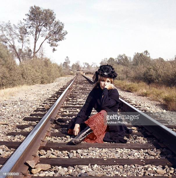 Kim Novak sits on train tracks in a scene from the film 'The Great Bank Robbery' 1969