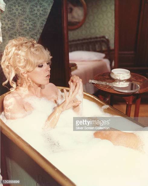Kim Novak US actress posing in a soapy bath a mirror rests on the table beside her in a studio portrait circa 1965