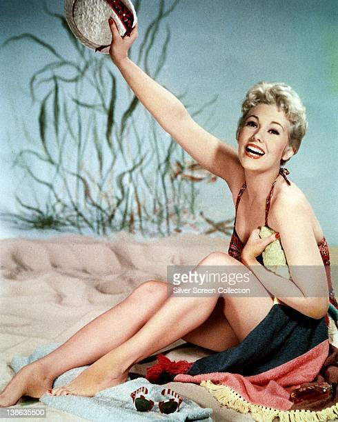 Kim Novak US actress smiling in a studio portrait designed to look like beach scene dressed in a swimsuit and sitting on a towel raising her right...