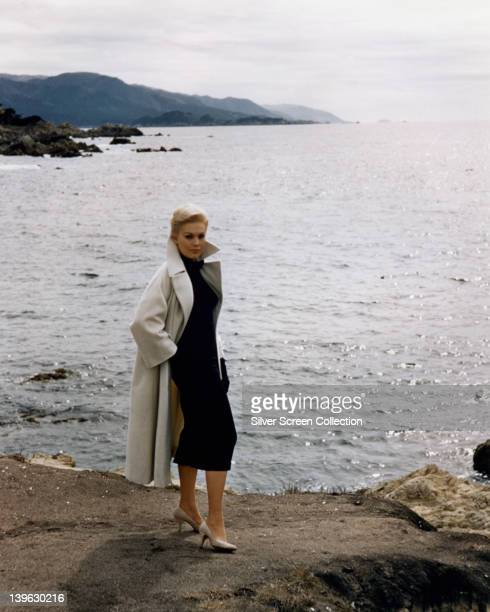 Kim Novak US actress wearing a white coat over a black dress with white shoes posing at the water's edge in a publicity portrait issued for the film...