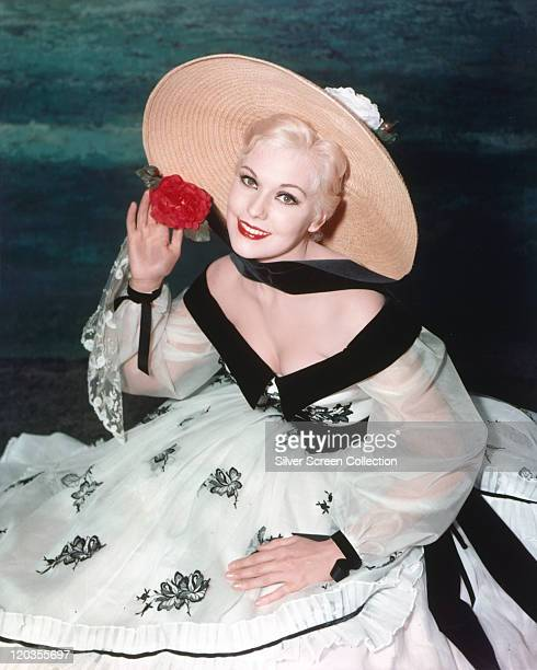 Kim Novak, US actress, wearing a white dress with black floral motifs and trim, and a wide-brimmed straw hat, posing with a red flowet in a studio...