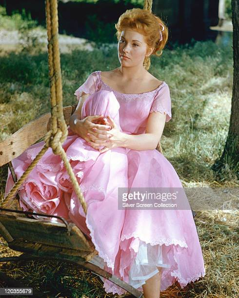 Kim Novak US actress with red hair wearing a long pink dress and sitting on a swing in a publicity still isuued for the film 'The Amorous Adventures...