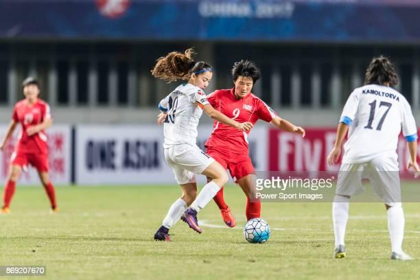 Kim Pom Ui of DPR Korea fights for the ball with Burkhonova Malika of Uzbekistan during their AFC U19 Women's Championship 2017 Group Stage A match...