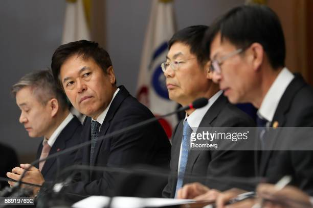 Kim Sangjo chairman of the Korea Fair Trade Commission right speaks as Ha Hyunhwoi chief executive officer of LG Corp left Park Jungho president and...