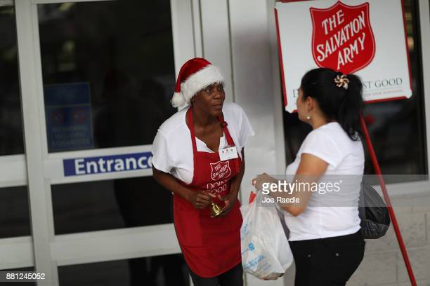 Kim Simmons a bellringer for the Salvation Army greets people as she collects donations in her red kettle on Giving Tuesday on November 28 2017 in...