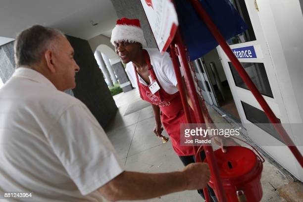 Kim Simmons a bellringer for the Salvation Army looks on as Alvaro Burgos makes a donation into her red kettle on Giving Tuesday on November 28 2017...