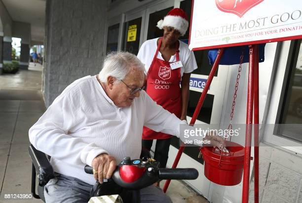 Kim Simmons a bellringer for the Salvation Army looks on as Murray Wiseman makes a donation into her red kettle on Giving Tuesday on November 28 2017...