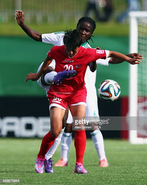 Kim So Hyang of Korea DPR is challenged by Ebere Okoye of Nigeria during the FIFA U20 Women's World Cup Canada 2014 Semi Final match between Korea...