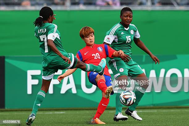 Kim Soyi of Korea Republic is challenged by Loveth Ayila and Ugo Njoku of Nigeria during the FIFA U20 Women's World Cup Canada 2014 group C match...